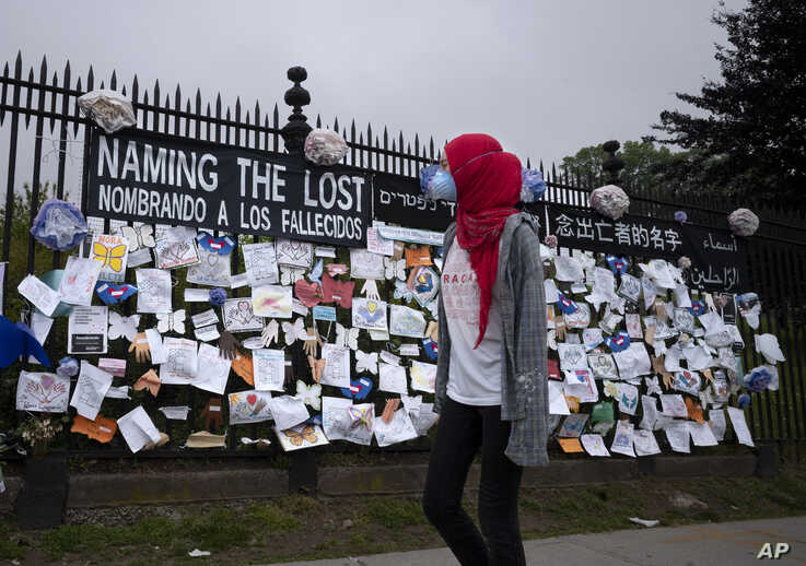 A woman passes a fence outside Brooklyn's Green-Wood Cemetery adorned with tributes to victims of COVID-19, May 28, 2020, in New York.