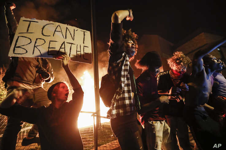 Protestors demonstrate outside of a burning Minneapolis 3rd Police Precinct, Thursday, May 28, 2020, in Minneapolis.