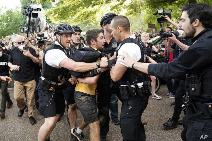 Uniformed U.S. Secret Service police detain a protester in Lafayette Park across from the White House as demonstrators protest.