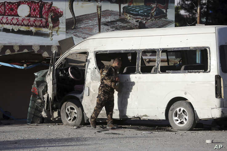 An Afghan security forces member inspects a bus carrying local TV station employees that hit a roadside bomb in Kabul, Afghanistan, Saturday, May 30, 2020.