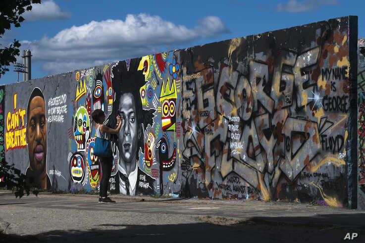 A woman takes a photo of a graffiti with the name of George Floyd, which is painted on a wall in the public park Mauerpark in Berlin, Germany, Saturday, May 30, 2020.