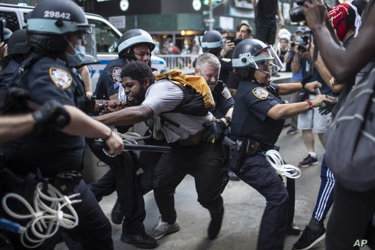 Police detain protesters as they march down the street during a solidarity rally for George Floyd, May 30, 2020.