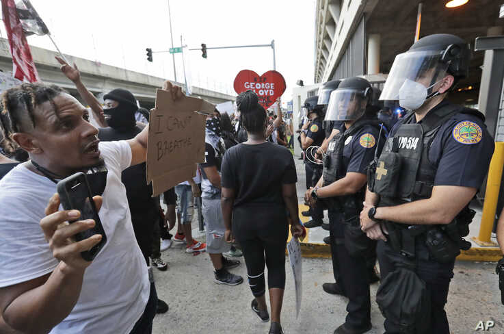 A protester confronts a line of police during a demonstration next to the city of Miami Police Department.