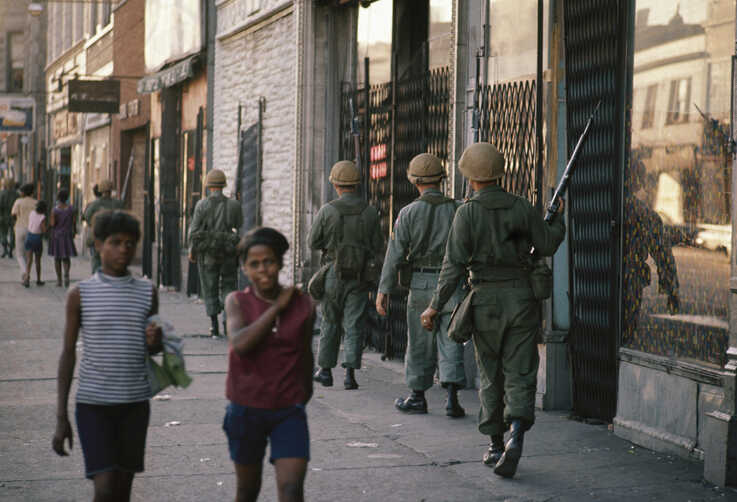 FILE - In this April 6, 1968 file photo, National Guard patrol the streets in Chicago, following rioting and violence