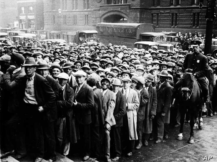 FILE - In this Oct. 9, 1930 file photo, thousands of unemployed people gather outside City Hall in Cleveland during the Great…