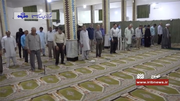 Iranian men adopt unusual social distancing at a reopened mosque in Kahnouj, Kerman province while ignoring a government requirement to wear face masks, in this May 5, 2020 report on Iranian state TV.