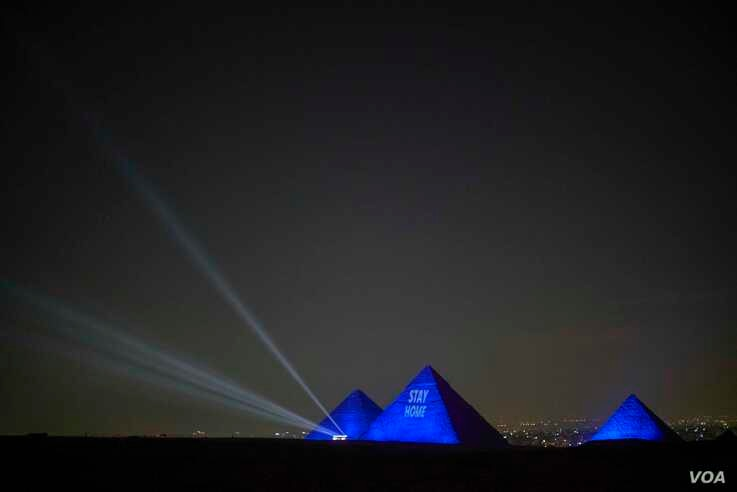 "The Great Pyramids of Giza are lit up with a message saying, ""Stay Home,"" April 18, 2020. (Hamada Elrasam/VOA)"