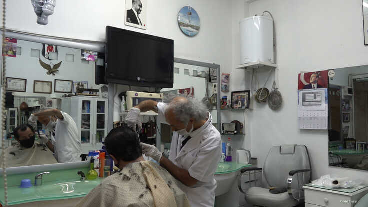 Tailor Yakup a customer of barber Gul Ali Simsek for forty years, welcomes the reopening but worries of a second lockdown if there are more infections. (D. Jones)