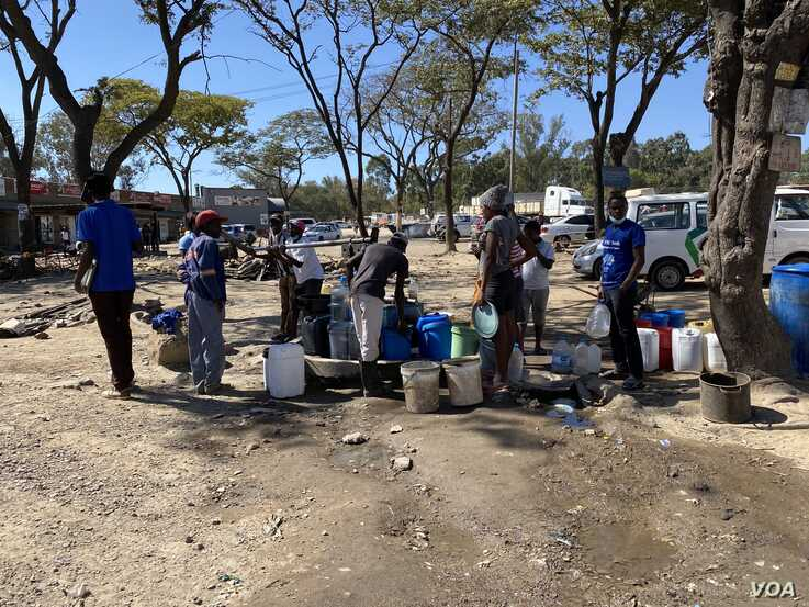 Residents queue for water (May 16, 2020) at a borehole sunk by the United Nations as part of efforts to contain water borne disease in Harare which has no reliable water supplies. Some residents that since COVID 19 requires hygiene it might a problem to fight it.  (Columbus Mavhunga/VOA)