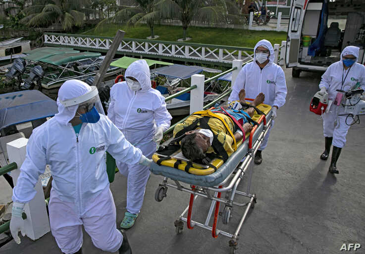 Medical personnel in protective gear transport a coronavirus patient to an ambulance boat, on Marajo island, Para state, Brazil, May 25, 2020.