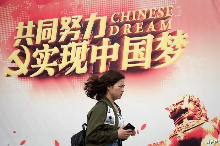 "FILE - A woman walks past a billboard promoting the ""Chinese Dream,"" a slogan associated with Chinese President Xi Jinping's ambitions for China, in Beijing, April 5, 2017."