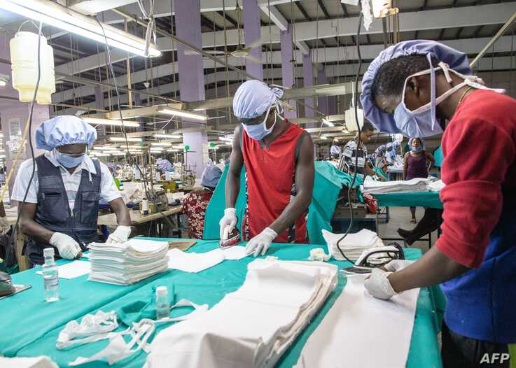FILE - Workers iron the fabric used for the production of personal protective equipment for coronavirus frontline health workers, in Accra, Ghana, April 17, 2020.