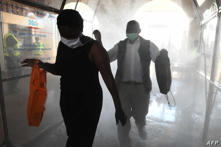 Passengers walk through a disinfectant tunnel before boarding the commuter train at the main railway station as a measure to contain the spread of the COVID-19, in Nairobi, Kenya, May 4, 2020.