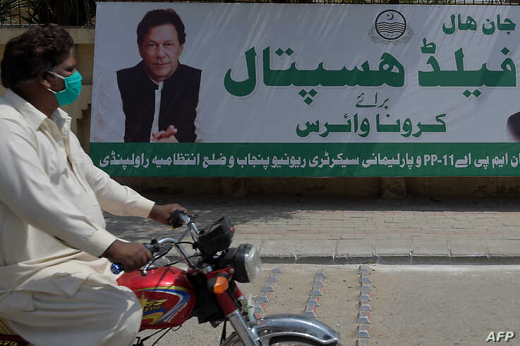FILE - A man wearing face mask rides his motorbike past a billboard showing a picture of Prime Minister Imran Khan along with a government advisory on coronavirus restrictions, in Rawalpindi, Pakistan, April 15, 2020.