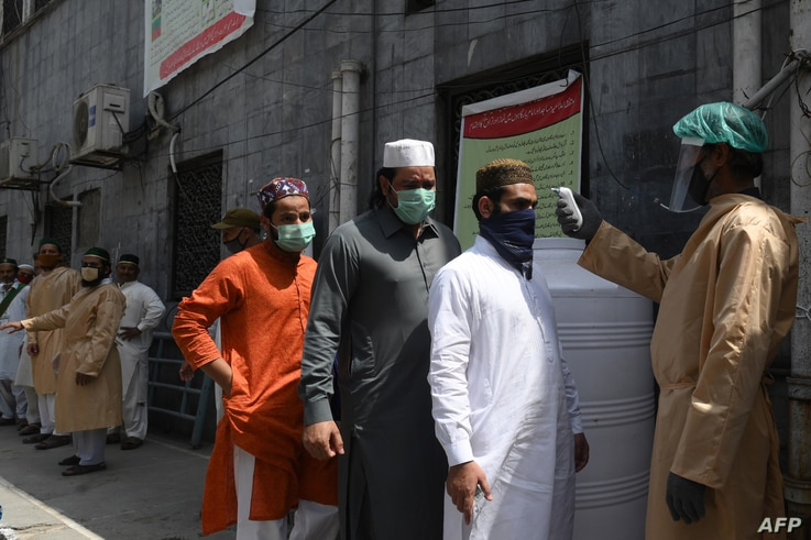 A man checks the body temperature of worshippers arriving for Friday prayers at a mosque in Lahore, Pakistan, May 1, 2020.