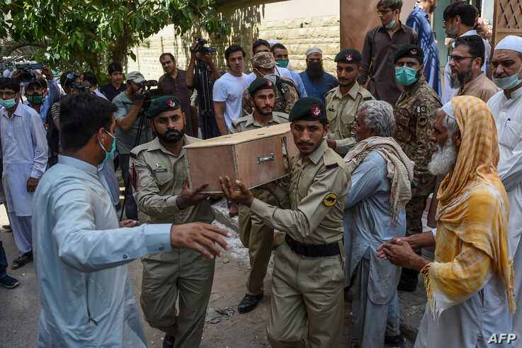 Army soldiers carry the coffin of a crash victim during a funeral a day after a Pakistan International Airlines aircraft crashed in a residential area in Karachi, Pakistan, May 23, 2020.