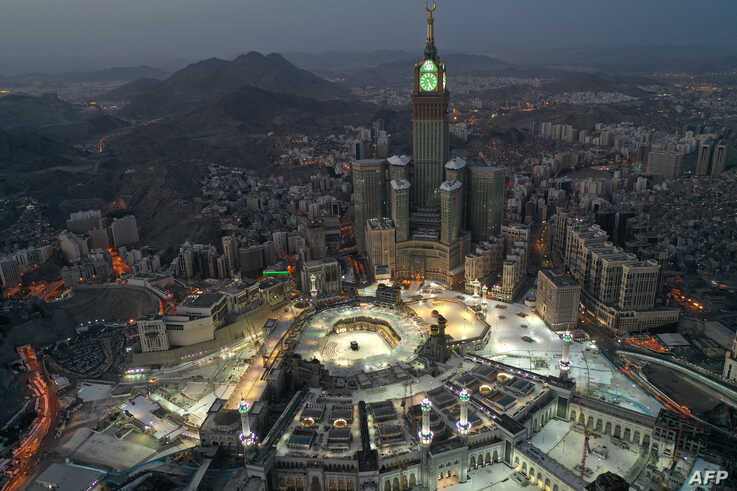 An aerial view of Saudi Arabia's holy city of Mecca, with the Abraj al-Bait Mecca Royal Clock Tower overlooking the Grand Mosque and Kaaba in the center, is seen during the early hours of Eid al-Fitr.