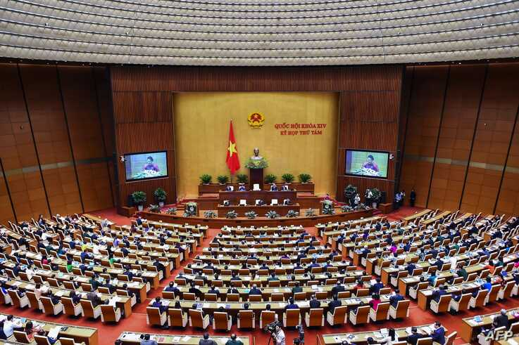 FILE- Vietnamese political leaders and members of parliament attend the National Assembly's session at the Parliament house in Hanoi, Oct. 21, 2019.