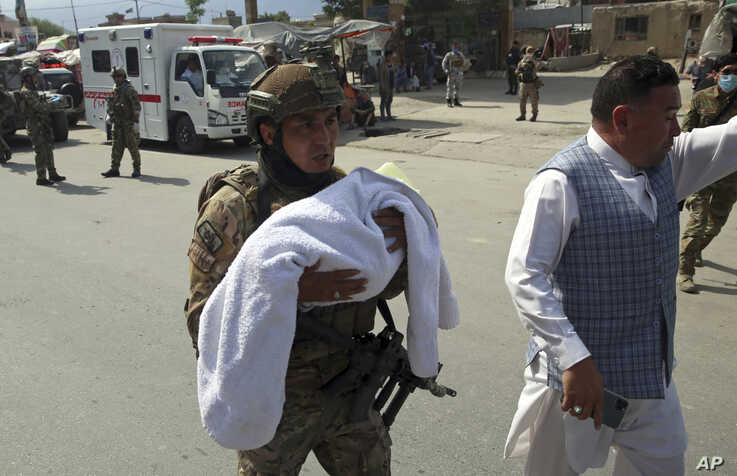 An Afghan security officer carries a baby after gunmen attacked a maternity hospital, in Kabul, May 12, 2020.