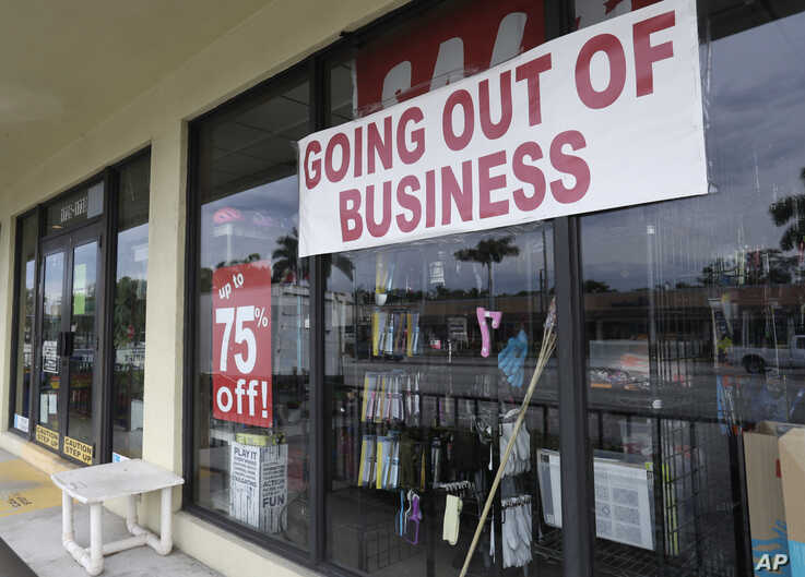 """FILE - A store front with a """"Going Out of Business"""" sign is seen in North Miami Beach, Florida, April 30, 2020."""