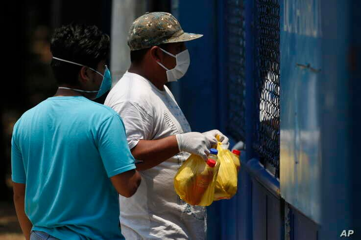 A health worker, right, stands behind a gate at an athletic dorm facility being used to house Guatemalans deported from the U.S., as a man brings food to the deportees in Guatemala City, April 17, 2020.