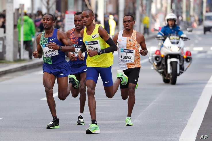 Ethiopea's Birhanu Legese, right, races with other runners on his way to winning the Tokyo Marathon in Tokyo, Japan, March 1, 2020.