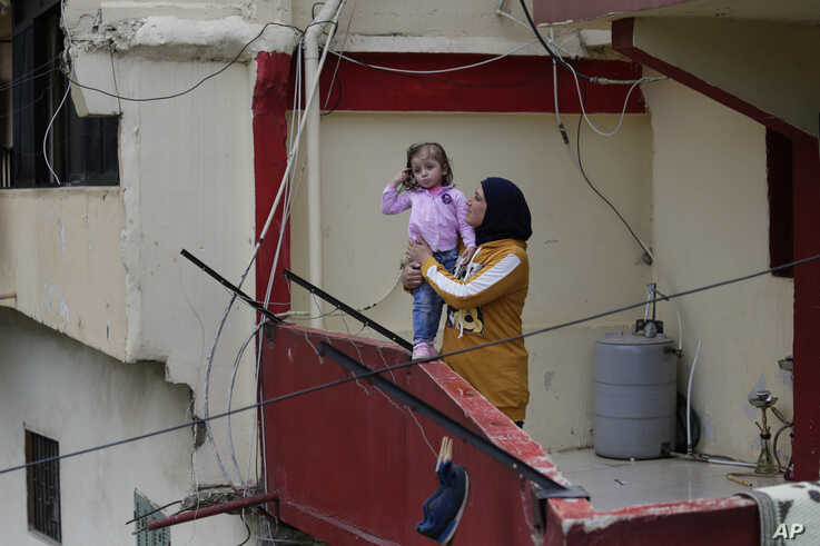 Faiqqa Homsi holds her daughter Maya, who was diagnosed with cancer, on her apartment balcony in the Mulawiya slum of the northern city of Tripoli, Lebanon, May 5, 2020.