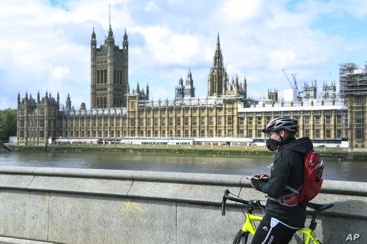 A man, wearing a protective mask, stands with his bike on the south bank of the River Thames against the backdrop of the Houses of Parliament, in London, Britain, May 1, 2020.