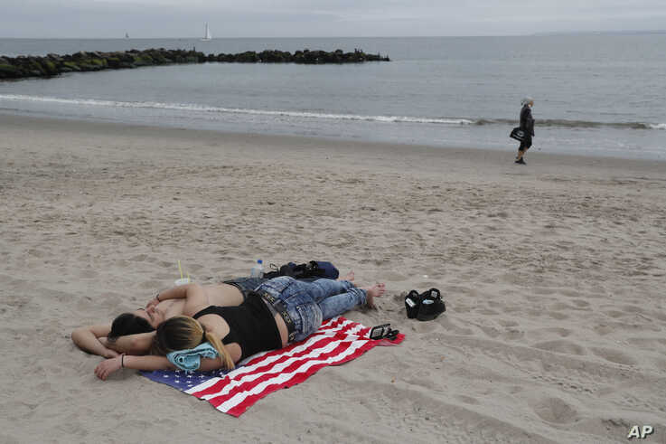 A couple lie on an American flag towel at Coney Island beach in New York during the coronavirus pandemic, May 24, 2020, during the Memorial Day holiday weekend.