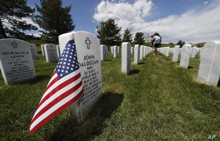 A flag stands next to the gravestone for a U.S. World War II veteran, at Fort Logan National Cemetery, in Sheridan, Colorado, May 23, 2020.
