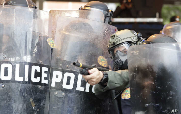 A policeman shoots rubber bullets at protesters throwing rocks and water bottles during a demonstration, May 30, 2020, in downtown in Miami.