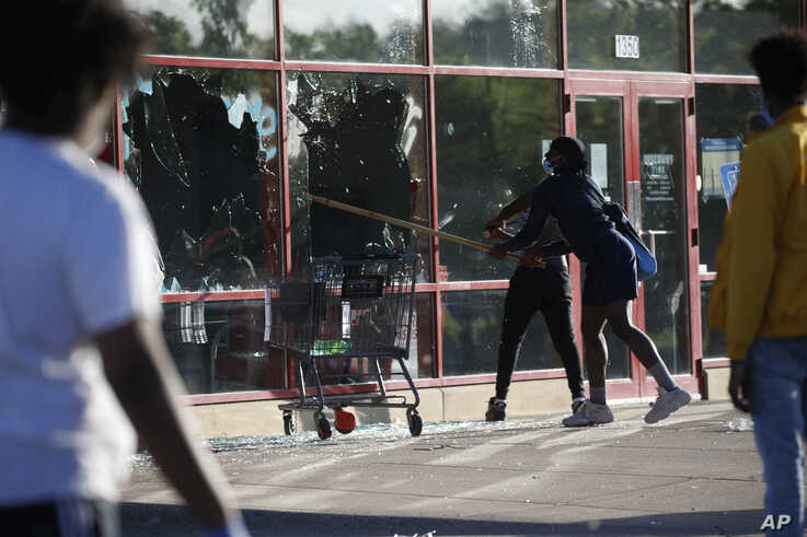 A man breaks a window at a tire store, May 28, 2020, in St. Paul, Minnesota.