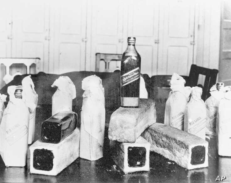 FILE - This June 12, 1924, photo shows bottles of Scotch whiskey smuggled in hollowed-out loaves of bread; location unknown.