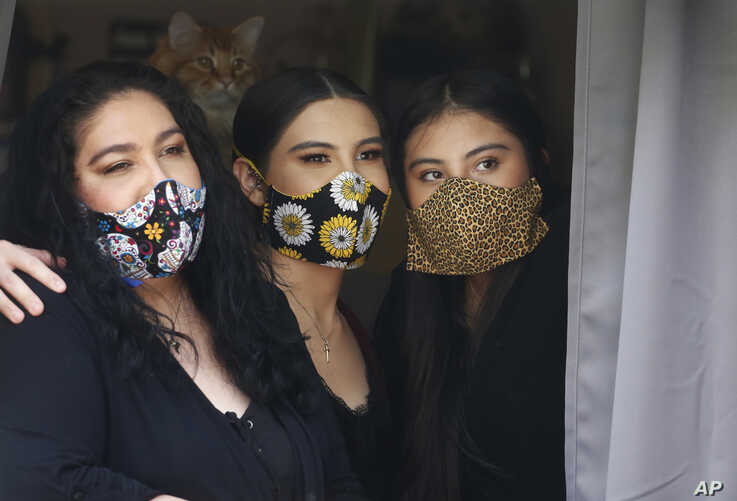Anissa Archuleta, center, sits at a window with her sister Alexis Archuleta, right, and her mother Jaime Ortega, at their home in Midvale, Utah, May 18, 2020.