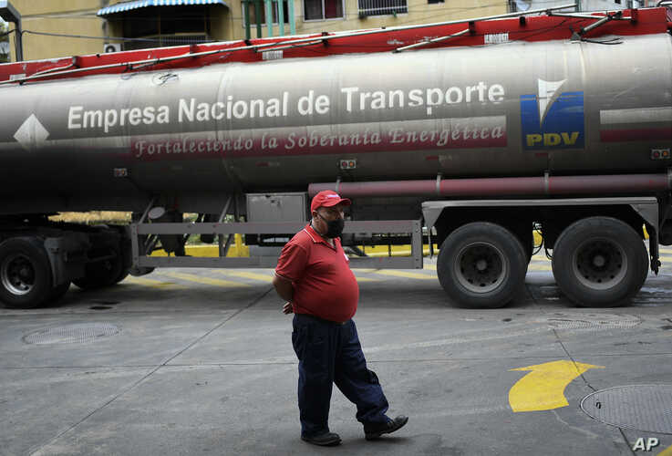 A worker wearing a face mask to protect against the coronavirus waits while a tanker truck fills the gasoline reservoir of a state oil company gas station, in Caracas, Venezuela, May 31, 2020.