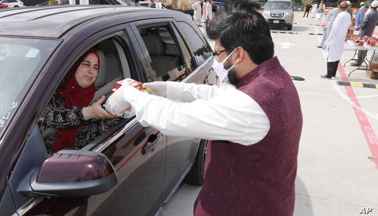 A woman accept treats during a drive-through Eid al-Fitr celebration outside a closed mosque in Plano, Texas, May 24, 2020.