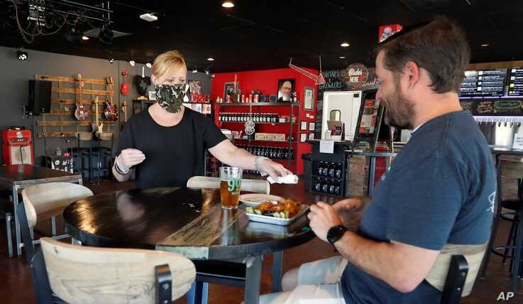 A customer being served a beer at Guitars & Growlers in Richardson, Texas. The restaurant was opened to customers on May 1 after restrictions due to COVID-19 were eased.