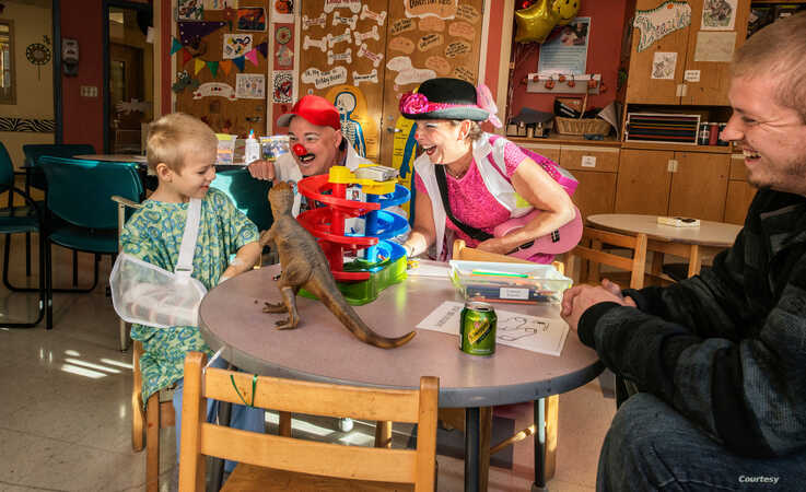 Jay Stewart (in red hat), in clown character as bumbling handyman Doc Skeeter, visits a young patient at Boston Children's Hospital. (Photo courtesy Dr. George Taylor)