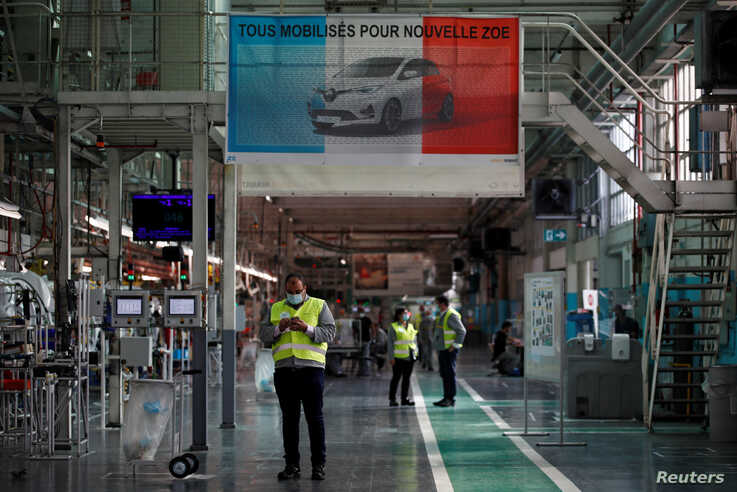 FILE - Workers, wearing face masks, are seen near the assembly line of Renault ZOE cars, as the French carmaker ramps up production with new security and health measures, in Flins, France, May 6, 2020.