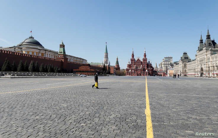 People walk across an empty Red Square in central Moscow, Russia, May 1, 2020.