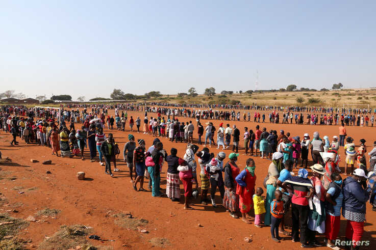 People stand in a queue to receive food aid amid the spread of the coronavirus disease (COVID-19), at the Itireleng informal settlement, near Laudium suburb in Pretoria, South Africa.