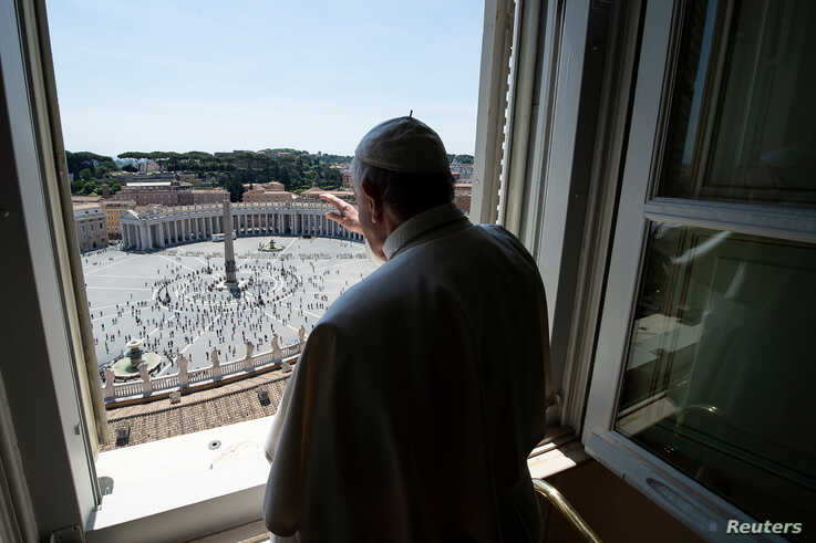 Pope Francis waves to people at St. Peter's Square after the Regina Coeli prayer, which was held without public participation due to the COVID-19 outbreak, at the Vatican, May 24, 2020. Vatican Media/Handout via REUTERS ATTENTION…