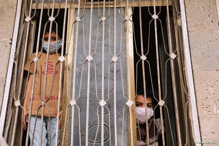 Children wearing protective masks look from behind a window during a 24-hour curfew amid concerns about the spread of the coronavirus disease (COVID-19), in Sana'a, Yemen, May 6, 2020.