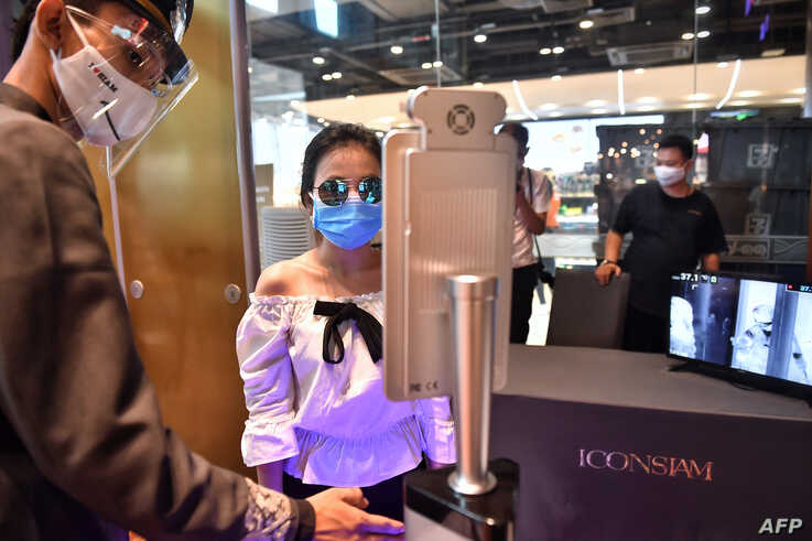 People stand in front of facial recognition software before entering the Icon Siam luxury shopping mall as it reopened after…
