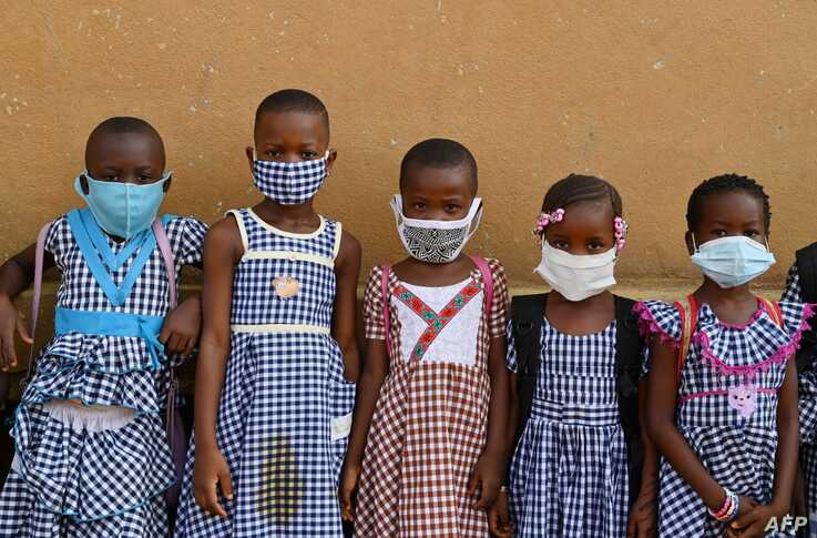 School children wearing face masks gather outside their classroom at a primary school in Attecoube, popular district of Abidjan…