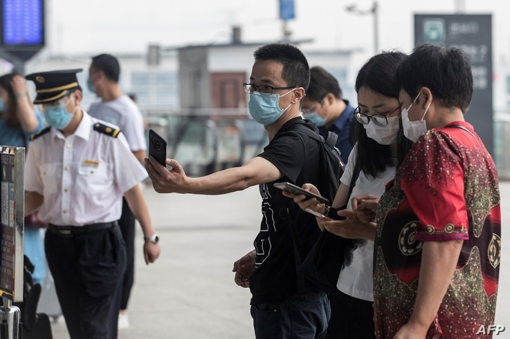 A man wears a face mask as he scans a code before entering the Wuhan Railway Station, in China's central Hubei province on May…