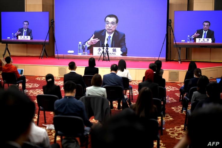 Chinese Premier Li Keqiang is seen on screens during a press conference held via online video link following the National…