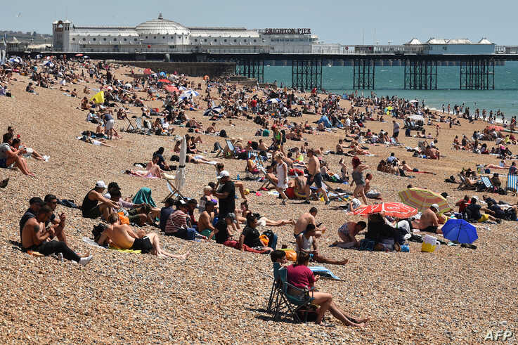 People sunbathe on the beach and cool off in the sea in Brighton on the south coast of England on May 31, 2020 on the eve of a…