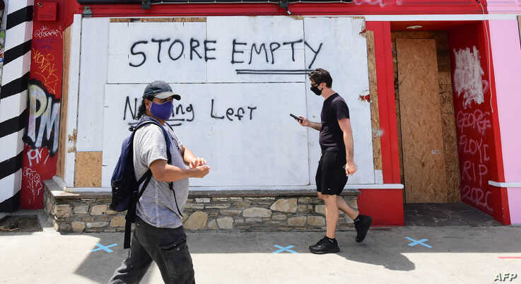 Pedestrians walk past boarded up storefronts on Melrose Avenue in Los Angeles, California on June 1, 2020, following a weekend…