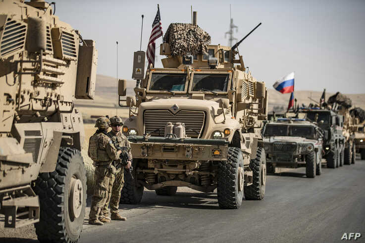 US military vehicles enclose Russian military vehicles in the northeastern Syrian town of al-Malikiyah (Derik) at the border…